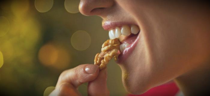 девушка кушает грецкий орех