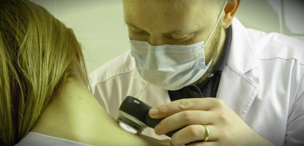 дерматолог осматривает кожу